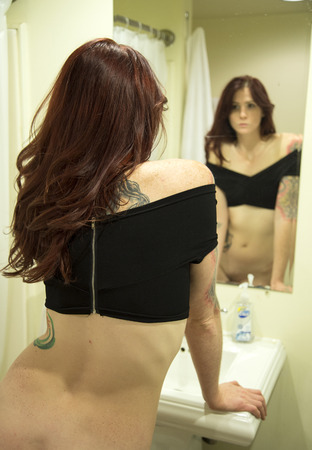 looking in mirror: Portrait of a beautiful young woman with red hair and blue eyes looking into a bathroom mirror.