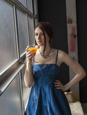 tomando jugo: Hermosa mujer joven con el pelo castaño y los ojos de beber un vaso de jugo de mango.