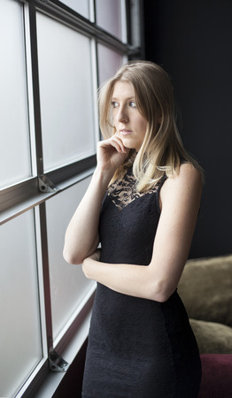 sexy black dress: Photo of a very attractive blonde in a sexy black dress looking out a window at a party. Stock Photo