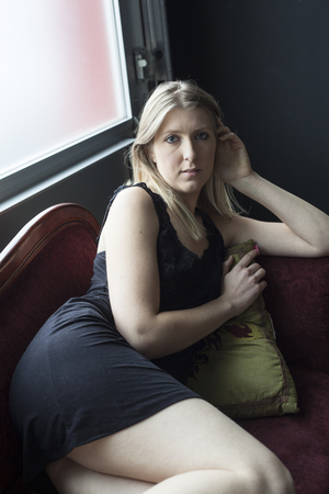 Photo of a very attractive blonde relaxing in a short black dress on a Victorian antique couch.