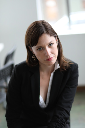 Photo of a very attractive business woman with brown hair and green eyes.