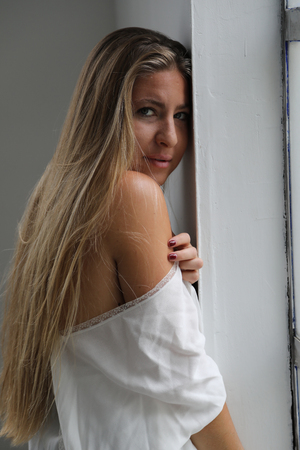 loose fitting: Photo of a very attractive blonde wearing a loose fitting white blouse. Stock Photo