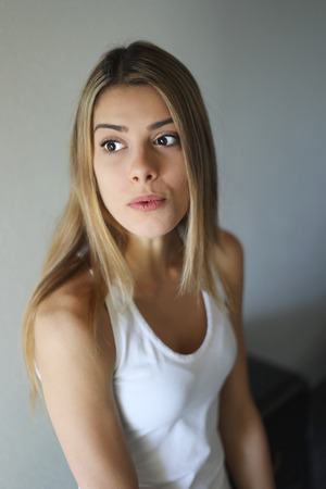 blonde females: Photo of a very attractive blonde woman with beautiful brown eyes in a white tank top.