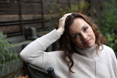 mujeres morenas: Foto de una mujer muy atractiva de 40 años de edad, con el pelo marrón y los ojos. Ella está sentada en su patio trasero en una mañana fresca del otoño. Foto de archivo