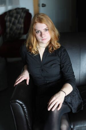 Photo of a very attractive redhead wearing a black button-down shirt.