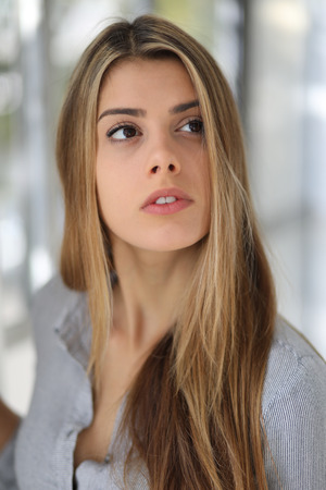 light brown eyes: Photo of a very attractive blonde woman with beautiful brown eyes in a blue top.