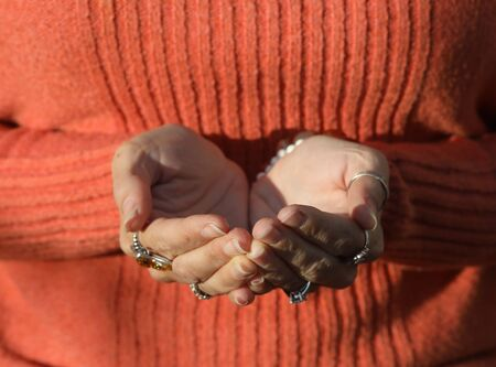 cupped: Photo of a woman in an orange sweater. She has her hands cupped in front of her.