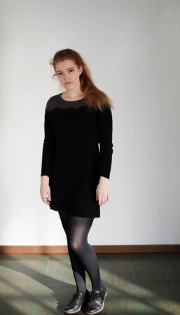 Photo of a very attractive redhead wearing a black dress and standing in front of a white wall. 写真素材