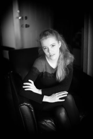 club dress: Black and white photo of a very attractive woman wearing a black dress and seated in a black leather club chair.