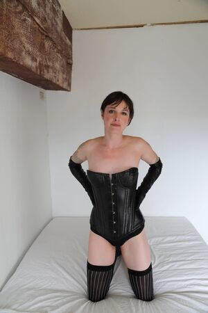 light complexion: Photo of a very attractive adult woman kneeling on a bed. She is wearing a leather corset and gloves, along with long pinstriped stockings.
