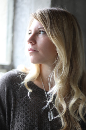 introspective: Photo of a very attractive blonde woman with beautiful brown eyes wearing a black top and sitting in front of a window.