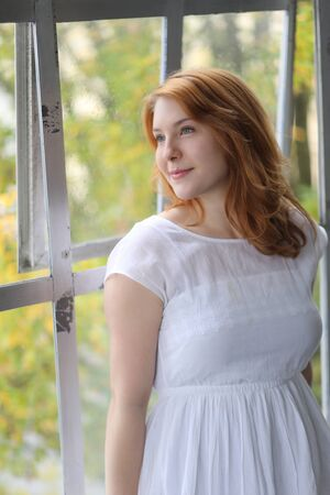 Head shot of a very attractive young woman with red hair and stunning blue eyes. She is wearing a a white dress.