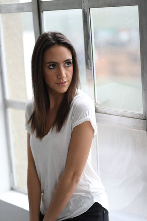 brown eyes: Photo of a very attractive young woman with brown hair and eyes. She is wearing a white tee shirt and sitting in front of a large window.