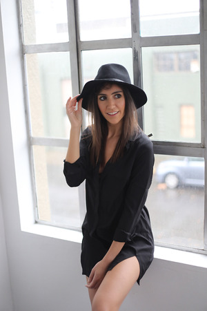 ojos hermosos: Photo of a very attractive young woman with brown hair and eyes. She is wearing a black shirt and black hat.