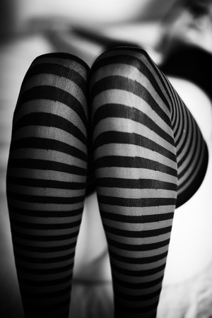 attractive woman: Photo of a very attractive adult woman lying on a bed. She is wearing striped stockings along with a black bra and panties.