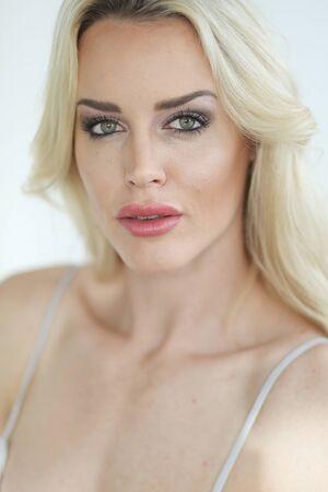 busty: Foto de una mujer rubia muy atractiva con hermosos ojos verdes que llevaba un vestido blanco escotado.