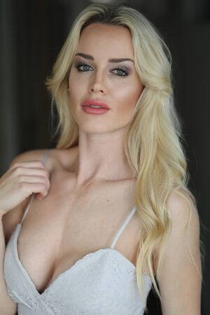 blonde females: Photo of a very attractive blonde woman with beautiful green eyes wearing a white wearing a lowcut white gown. Stock Photo