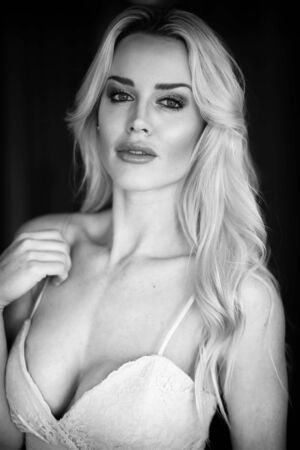 Black and white photo of a very attractive blonde woman wearing a low cut white gown.