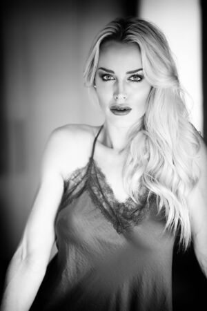 Black and white photo of a very attractive blonde woman wearing  dark gray silk lingerie. She is looking straight at the camera.