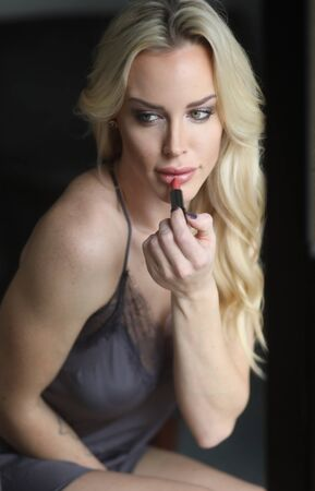 Photo of a very attractive blonde woman with beautiful green eyes wearing a dark gray silk lingerie. She is putting on her lipstick and looking into a mirror.