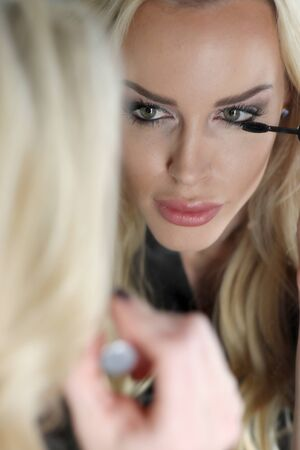 Photo of a very attractive blonde woman with beautiful green eyes wearing a dark gray silk robe. She is putting on her mascara and looking into a mirror.