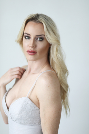 Photo of a very attractive blonde woman with beautiful green eyes wearing a white wearing a lowcut white gown. Stock Photo