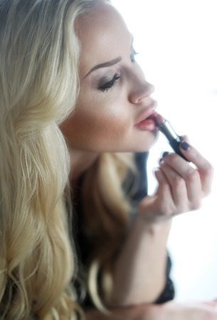 Photo of a very attractive blonde woman with beautiful green eyes. She is putting on her lipstick and looking into a mirror.