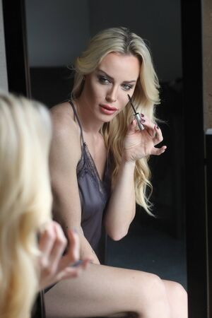 Photo of a very attractive blonde woman with beautiful green eyes wearing a dark gray silk lingerie. She is putting on her Macara and looking into a mirror.