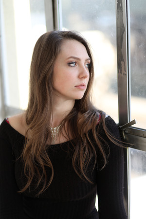 Photo of a very attractive woman with brown hair. She is looking longingly out of a window.