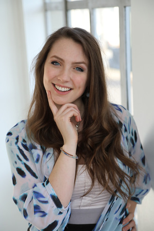 Office women: Photo of a very attractive woman with brown hair and blue eyes shot against a window. Stock Photo