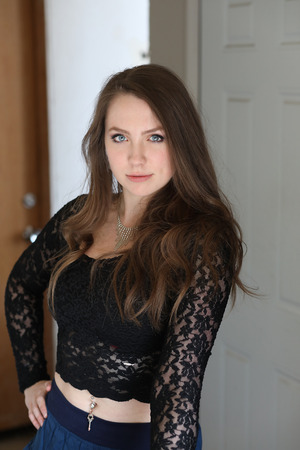 swagger: Photo of a very attractive woman with brown hair and blue eyes shot in a doorway. She is wearing a sexy, black lace shirt and has some swagger. Stock Photo