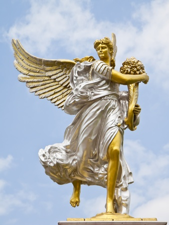 Statue of angel holding a bouquet of flowers.