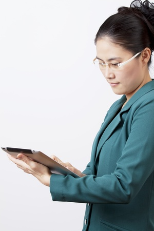 Asian business woman. Are focusing on touch tablet . Stock Photo - 12363570