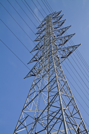 High voltage towers , on blue sky background  photo