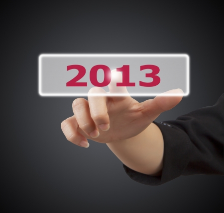 woman hand touching button 2013 keyword, on gray background photo