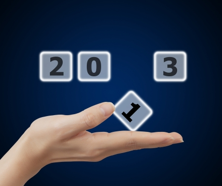 woman hand holding button 2013 keyword, on blue background photo
