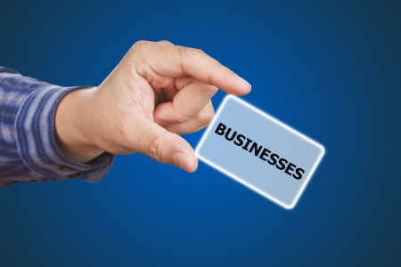 assessment system: man hand touching button businesses keyword, on blue background