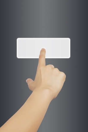 Woman hand touching button on gray background  photo