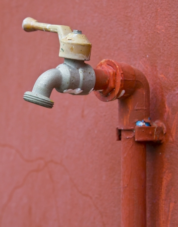 Faucet on red wall, a photo close-up  photo