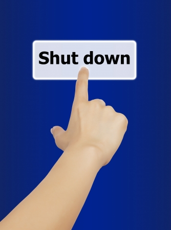 woman hand touching button shut down keyword, on blue background  photo