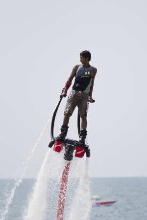 water skier: CHONBURI, THAILAND-DECEMBER 8  Unidentified man showing usage water machine flyboard in Jet Ski King Editorial