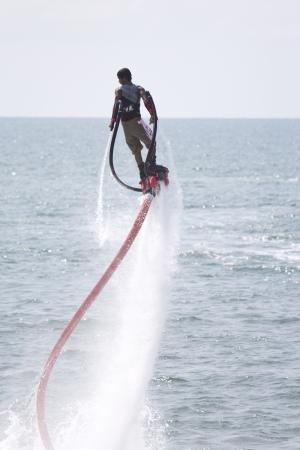 jet skier: CHONBURI, THAILAND-DECEMBER 8  Unidentified man showing usage water machine flyboard in Jet Ski King Editorial