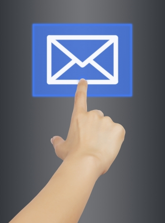 woman hand touching mail button, on gray background  photo