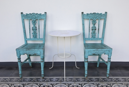 Old blue wooden chair with table, on the tiled floor. Stock Photo