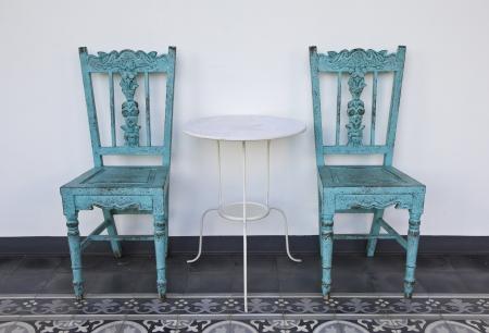 Oude blauwe houten stoel met tafel, op de tegelvloer. Stockfoto