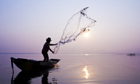 Fishermen are catching fish with cast a net in the reservoir.  Stock Photo