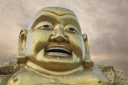 smiling buddha: smiling Buddha statue, Evening sky background.