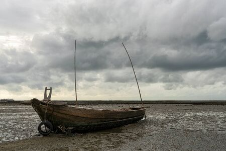 Rowing boat in the sea, with rain clouds background. Stock Photo