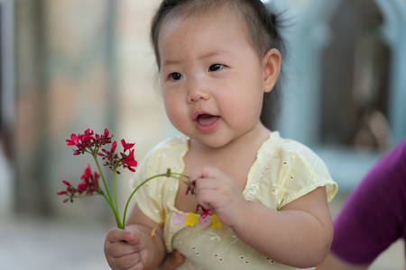 Happy Asian baby girl with Thai traditional dress, Holding flowers in hand.