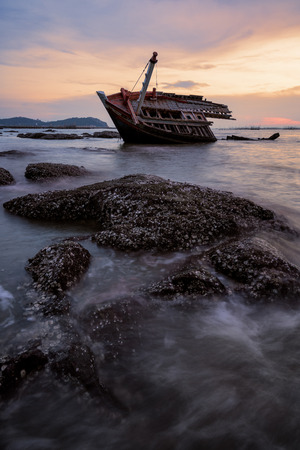 Shipwreck with rocks during sunset.